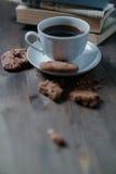 O copo e as cookies de café são ao lado da pilha de livros imagem de stock