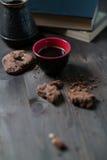 O copo e as cookies de café são ao lado da pilha de livros fotos de stock royalty free
