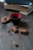 O copo e as cookies de café são ao lado da pilha de livros foto de stock royalty free