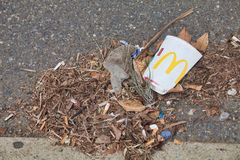 O copo e a maca vazios de McDonalds sairam pelo lado da estrada imagens de stock royalty free