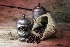 O copo e os feijões de café de prata no pano de saco ensacam no backgroun de madeira Foto de Stock