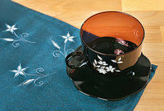 O copo e os pires de China em um azul bordaram guardanapo Imagem de Stock