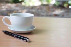 O copo e a pena de café são colocados em uma tabela de madeira marrom e têm c imagem de stock