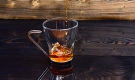 O copo que derrama com água ou chá com espirra no fundo de madeira escuro Conceito do chá da fabricação de cerveja Vidro com o ch foto de stock royalty free