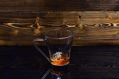 O copo que derrama com água ou chá com espirra no fundo de madeira escuro O vidro com o chá que derrama com líquido com espirra imagens de stock royalty free