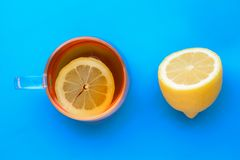 O copo transparente do chá com limão, cortou recentemente o meio limão no fundo azul imagem de stock