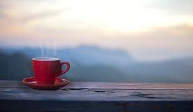 O copo vermelho com café na tabela sobre montanhas ajardina Fotografia de Stock Royalty Free