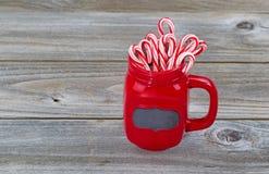 O copo vermelho encheu-se com os bastões de doces para a época natalícia Fotografia de Stock Royalty Free