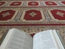 O Corão santamente em inglês e em árabe Oriental-teste padrão bonito em um tapete denominado imagens de stock royalty free
