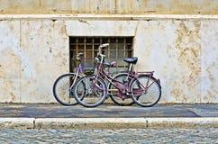 O ` cor-de-rosa s de duas mulheres Bicycles em uma rua urbana fotos de stock royalty free