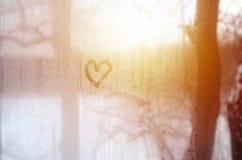 O coração é pintado no vidro misted no inverno imagens de stock