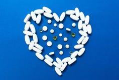 O coração apresentou comprimidos no fundo azul Conceito da doen?a card?aca imagem de stock royalty free