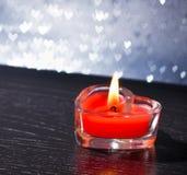 O coração ardente vermelho deu forma à vela no bokeh de prata dos corações Imagens de Stock Royalty Free