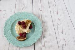 O coração belga macio caseiro deu forma a waffles com as framboesas e os figos, cobertos com o mel na placa do azul de turquesa Imagens de Stock Royalty Free