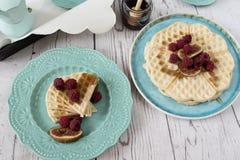 O coração belga macio deu forma a waffles com as framboesas e os figos, cobertos com o mel na placa do azul de turquesa Imagem de Stock Royalty Free