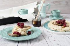 O coração belga macio deu forma a waffles com as framboesas e os figos, cobertos com o mel na placa do azul de turquesa Imagem de Stock