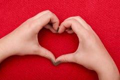 O coração bonito das mãos do ` s das mulheres em um vermelho fez malha o fundo fotos de stock