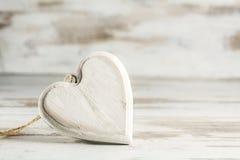O coração branco do vintage da madeira contra um branco pintou o backg de madeira Imagens de Stock