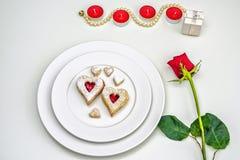 O coração caseiro deu forma a cookies de Linzer da amêndoa na placa branca Aniversário estabelecido romântico do ffor das rosas v fotografia de stock royalty free