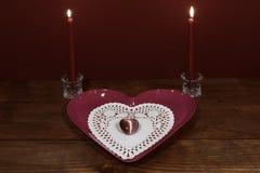 O coração cor-de-rosa deu forma à placa com dollie e à pedra preciosa, duas velas vermelhas nos suportes de cristal na tabela de  fotos de stock royalty free