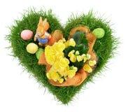 O coração dá forma à grama com os ovos da páscoa no fundo branco foto de stock