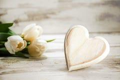 O coração da madeira e das tulipas em um branco pintou o fundo de madeira, r Foto de Stock Royalty Free