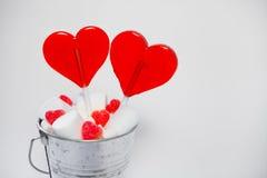 O coração de dois pirulitos deu forma na cubeta pequena com os doces no branco Fotos de Stock Royalty Free
