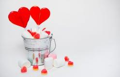 O coração de dois pirulitos deu forma na cubeta pequena com os doces no branco Imagem de Stock Royalty Free