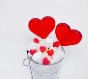 O coração de dois pirulitos deu forma na cubeta pequena com os doces no branco Imagens de Stock Royalty Free