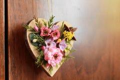 O coração de madeira decorou com as flores coloridas artificiais que penduram na porta de armário Foto de Stock Royalty Free