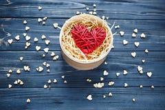 O coração de madeira vermelho encontra-se na caixa na tabela escura com mini corações ao redor Valentim do St fotografia de stock royalty free