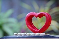 O coração de madeira vermelho pôs sobre a guitarra para o amor sobre o fundo da natureza Fotos de Stock