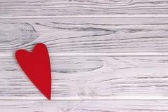 O coração de madeira vermelho que pendura no branco pintou o fundo de madeira rústico Imagens de Stock