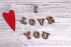 O coração de madeira vermelho que pendura no branco pintou o fundo de madeira rústico com rotulação eu te amo Imagem de Stock Royalty Free