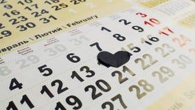 O coração de papel preto cobre o número 14 em fevereiro no calendário O dia de Valentim, o amor e coração quebrado filme