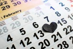 O coração de papel preto no calendário cobre em fevereiro o número 14 Coração quebrado foto de stock