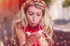O coração de sopro da jovem mulher deu forma a confetes coloridos no ar fim foto de stock royalty free