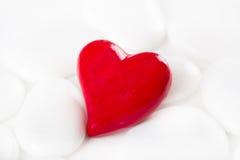 O coração decorativo vermelho em um fundo branco com as pedras para cumprimenta Foto de Stock