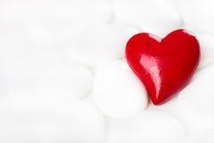 O coração decorativo vermelho em um fundo branco com as pedras para cumprimenta Imagem de Stock