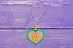 O coração deu forma à joia para o dia do ` s do Valentim O dia de Valentim sentiu a joia do coração no fundo de madeira roxo Pres fotografia de stock royalty free