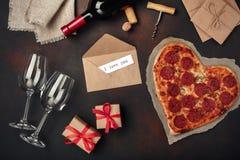 O coração deu forma à pizza com a mussarela, sausagered e a garrafa de vinho, fotografia de stock
