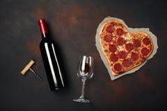 O coração deu forma à pizza com a mussarela, sausagered e a garrafa de vinho, o copo de vinho e o corkscrew Cartão do dia de Vale imagem de stock