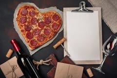 O coração deu forma à pizza com a mussarela, sausagered, a garrafa de vinho, o corkscrew e a tabuleta no fundo oxidado imagens de stock royalty free