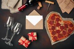 O coração deu forma à pizza com a mussarela, sausagered, garrafa de vinho, dois copo de vinho, caixa de presente no fundo oxidado fotos de stock