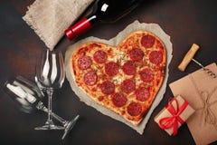 O coração deu forma à pizza com a mussarela, sausagered, garrafa de vinho, dois copo de vinho, caixa de presente no fundo oxidado foto de stock royalty free