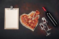 O coração deu forma à pizza com a mussarela, sausagered, a garrafa de vinho, o dois copo de vinho e a tabuleta no fundo oxidado imagem de stock