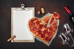 O coração deu forma à pizza com a mussarela, sausagered, a garrafa de vinho, o dois copo de vinho e a tabuleta no fundo oxidado foto de stock royalty free