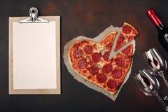O coração deu forma à pizza com a mussarela, sausagered, a garrafa de vinho, o dois copo de vinho e a tabuleta no fundo oxidado imagens de stock royalty free