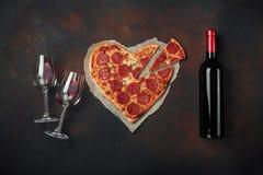 O coração deu forma à pizza com a mussarela, sausagered, a garrafa de vinho e o copo de vinho dois Cartão do dia de Valentim no f foto de stock