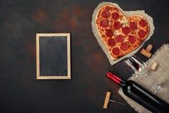 O coração deu forma à pizza com a mussarela, sausagered com uma garrafa de imagem de stock royalty free